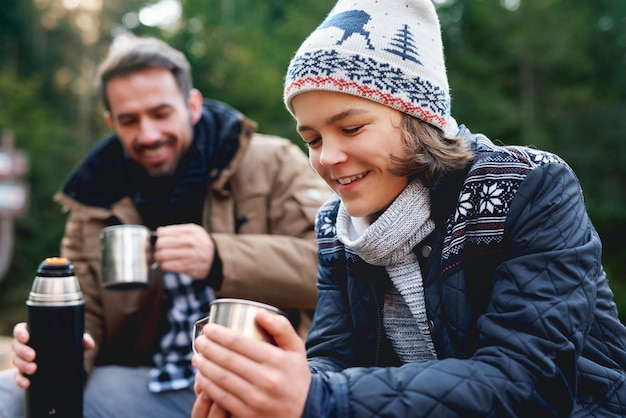 Zbliżenie na uśmiechniętego nastoletniego chłopca pijącego herbatę w lesie