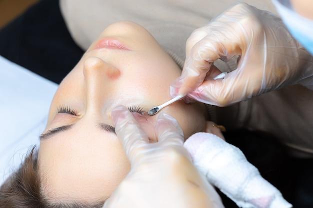 Zbliżenie na usunięcie nadmiaru pigmentu bawełnianą gąbką modelu powieki
