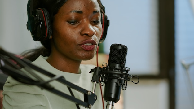 Zbliżenie na vlogera afro kobieta, który tworzy nowy blog wideo w domowym studiu rozmawiając w profesjonalnym mikrofonie z publicznością. przemawiając podczas transmisji na żywo, bloger dyskutujący w podkaście w słuchawkach.