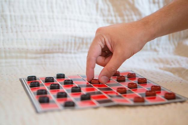 Zbliżenie na warcaby. czarno-czerwona mapa. ręka trzyma chip. gry dla rozwoju logiki