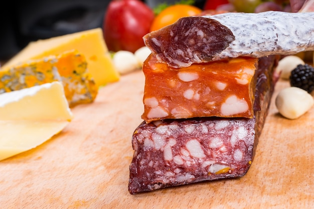 Zbliżenie na wędzone i wędliny na desce serów dla smakoszy - apetyczne jedzenie martwa natura z miejscem na kopię