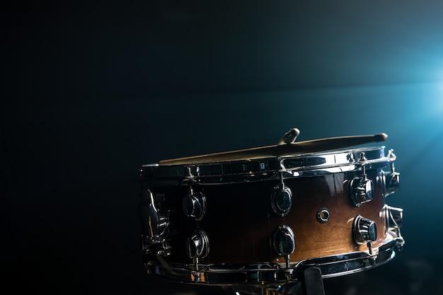 Zbliżenie na werbel, instrument perkusyjny na ciemnym tle z pięknym oświetleniem, kopia przestrzeń.