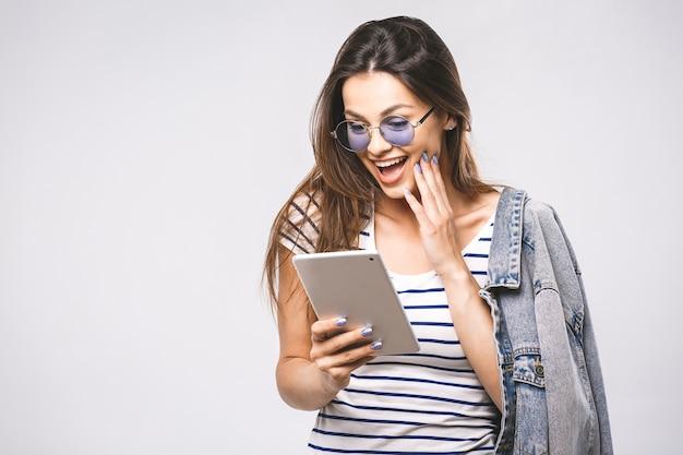 Zbliżenie na wesoły młody kaukaski kobieta pokazuje wyświetlacz komputera typu tablet
