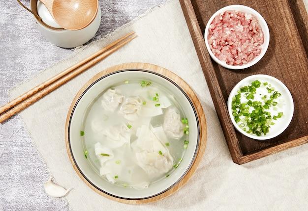 Zbliżenie na widok z góry na zupę z kluskami, surowe mięso, pałeczki i posiekaną zieloną cebulę
