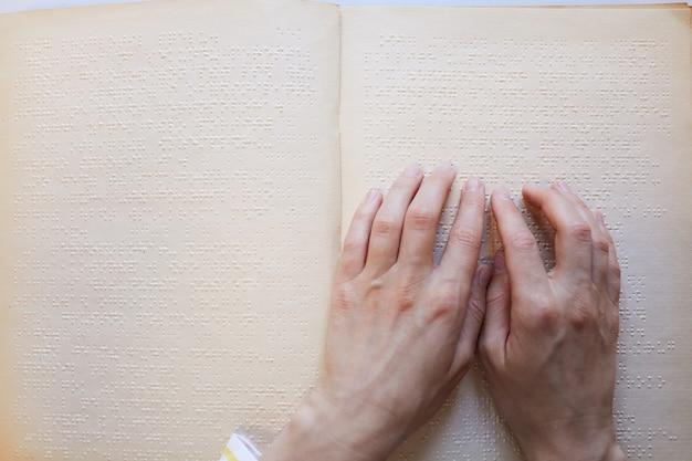 Zbliżenie na widok z góry nierozpoznawalnej osoby niewidomej czytającej miejsce na kopię książki braille'a