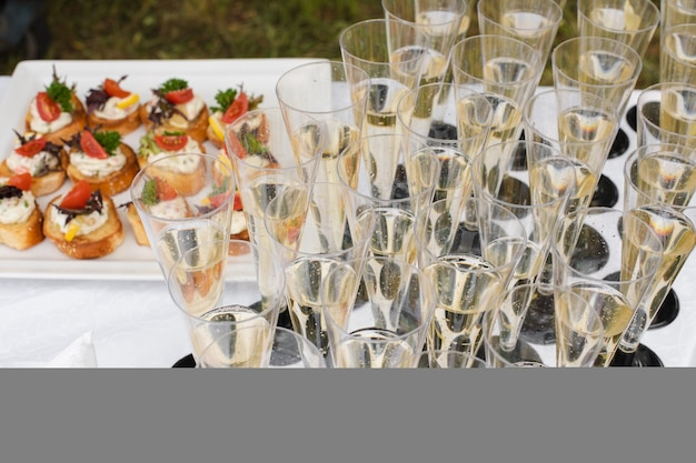 Zbliżenie na wiele kieliszków szampana lub innego napoju gazowanego z grzankami z warzywami i twarogiem na weselu lub bankiecie. uroczyste przyjęcie.