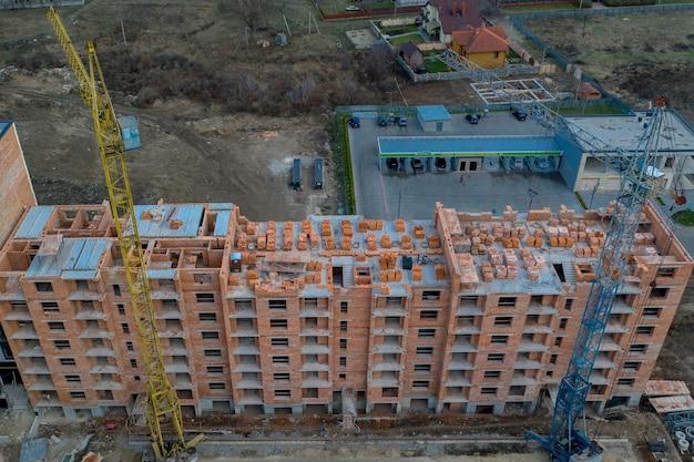 Zbliżenie na wielokondygnacyjny budynek mieszkalny w budowie z czerwonej cegły z częścią dźwigu.