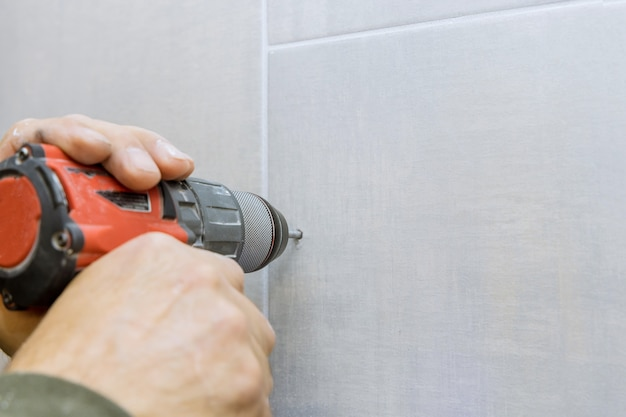 Zbliżenie na wiercenie otworu w płytkach ceramicznych na ścianie łazienki