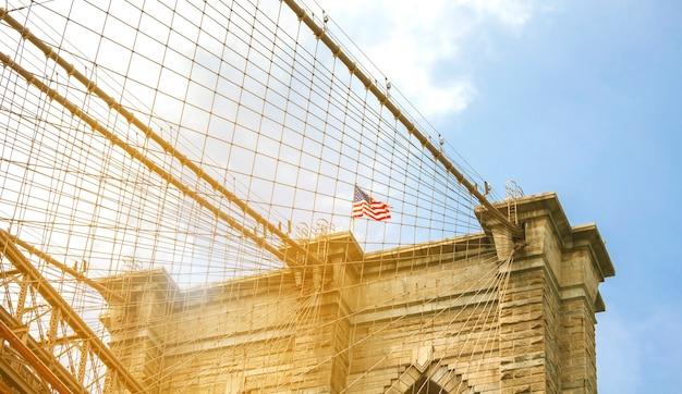Zbliżenie na wieże i amerykańską flagę nad brooklyn bridge w nowym jorku york