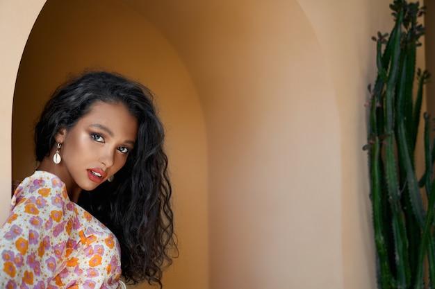 Zbliżenie na wspaniałą dziewczynę w kolorowej bluzce, opierając się o ścianę