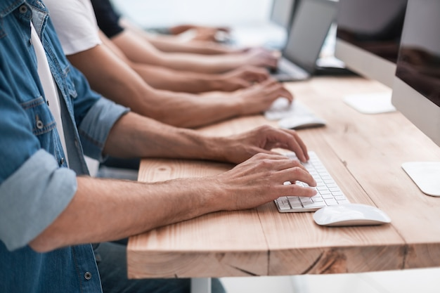 Zbliżenie na współpracowników pracujących na ich komputerach