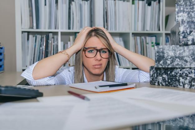 Zbliżenie na wyczerpaną blond sekretarkę patrzącą i trzymającą się za głowę rękami with
