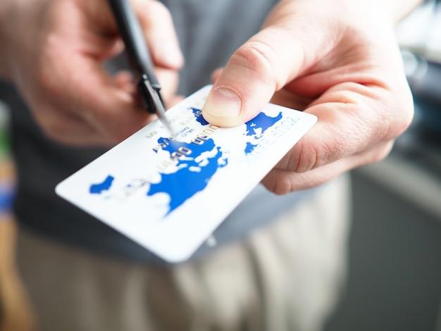Zbliżenie na wygasłą kartę kredytową, osoba tnąca plastikowy przedmiot nożyczkami. ograniczona płatność lub nadmierne wydatki, niszczenie przedmiotu. wydawanie pieniędzy lub spłacanie pożyczki