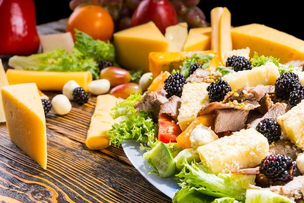 Zbliżenie na wykwintną sałatkę ze świeżych warzyw, jeżyn, sera i mięsa na rustykalnym drewnianym stole otoczonym klinami sera i innymi składnikami