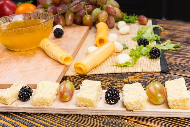 Zbliżenie na wykwintne sery i świeże owoce ułożone na wąskiej desce z deską do krojenia i składnikami w tle