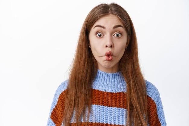 Zbliżenie na zabawną zaskoczoną dziewczynę, zmarszczone usta i gapienie się z zainteresowaniem i podekscytowaniem z przodu, stojąc w swetrze na białej ścianie