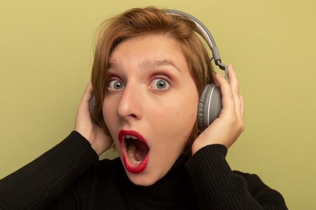 Zbliżenie na zachwyconą młodą blondynkę w słuchawkach, kładącą na nich ręce
