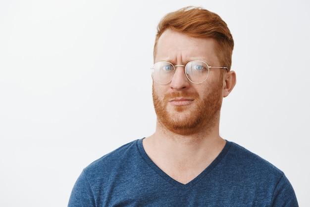 Zbliżenie na zaniepokojonego, przerażonego rudowłosego faceta w okularach, który kuli się od czegoś dziwnego