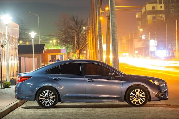 Zbliżenie na zaparkowany samochód na poboczu drogi w nocy z niewyraźnym widokiem na sygnalizację świetlną