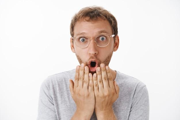 Zbliżenie na zaskoczonego, zszokowanego i zafascynowanego czarującego mężczyznę rasy kaukaskiej z brodą w okularach, mówiącego wow, składając otwarte usta i trzymając dłonie nad wargą, zatroskany i zdumiony
