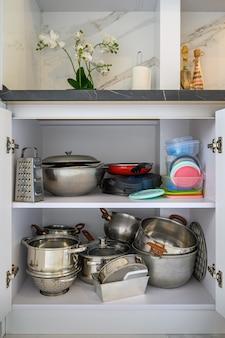 Zbliżenie na zawartość szafki nowoczesnej kuchni z typowymi naczyniami