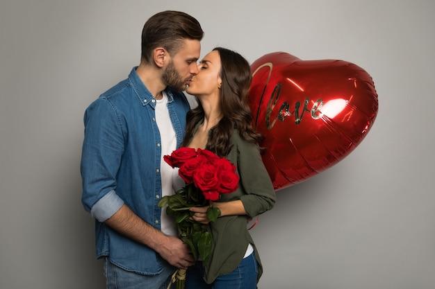 Zbliżenie na zdjęcie atrakcyjnego mężczyzny, który trzyma w rękach czerwone pudełko, podczas gdy jego wspaniała dziewczyna uśmiecha się do niego po otrzymaniu bukietu róż.