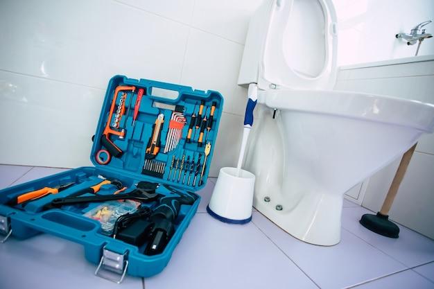 Zbliżenie na zdjęcie ceramicznej miski toaletowej w domowej łazience z pudełkiem narzędzi