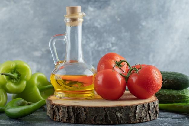 Zbliżenie na zdjęcie czerwonego pomidora z zieloną papryką i butelką oleju