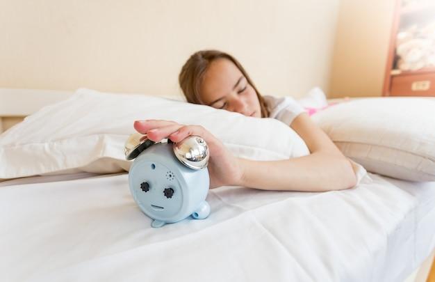 Zbliżenie na zdjęcie dziewczyny sięgającej po budzik