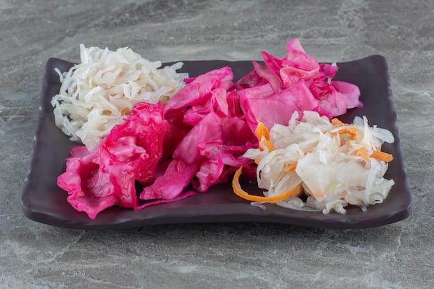 Zbliżenie na zdjęcie kiszonej kapusty i różowej kapusty na czarnym talerzu
