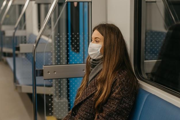 Zbliżenie na zdjęcie kobiety w medycznej masce na twarz, aby uniknąć rozprzestrzeniania się koronawirusa, siedzącej samotnie w nowoczesnym wagonie metra. dziewczyna w masce chirurgicznej trzyma dystans społeczny w pociągu metra.