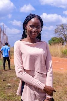 Zbliżenie na zdjęcie ładnej afrykańskiej damy, która uśmiecha się i pozuje