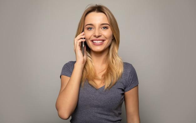 Zbliżenie na zdjęcie ładnie wyglądającej dziewczyny w swobodnym ubraniu, która rozmawia przez telefon, uśmiecha się i gestykuluje lewą ręką.