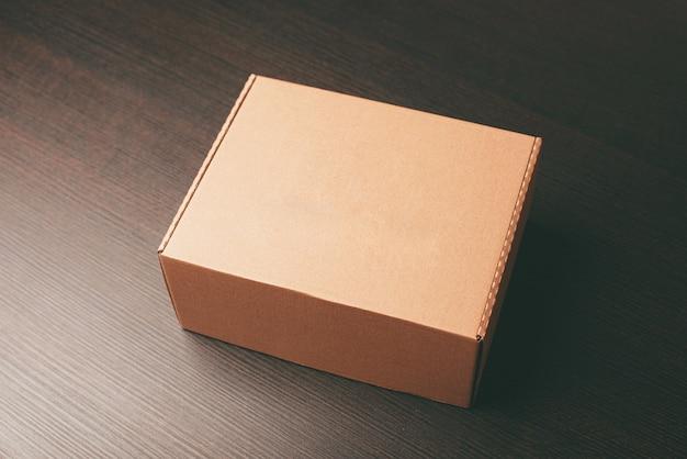 Zbliżenie na zdjęcie makiety pudełka na lunch nad ciemnym drewnianym stołem
