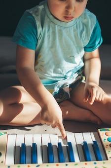 Zbliżenie na zdjęcie małego chłopca grającego na pianinie siedzącego na podłodze skoncentrowanego
