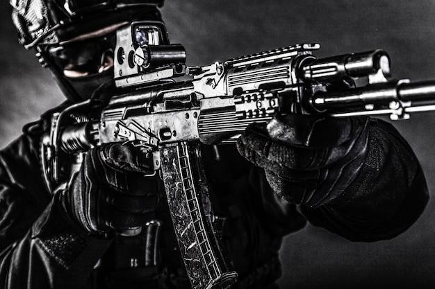 Zbliżenie na zdjęcie nowoczesnego karabinu szturmowego z celownikiem kolimatorowym w rękach policyjnego bojownika grupy operacji specjalnych w czarnym mundurze, kasku i twarzy ukrytej za maską, nienasycone, niskie strzelanie studyjne
