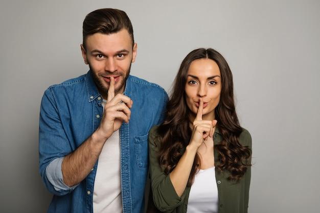 Zbliżenie na zdjęcie pięknej pary, która pozuje z przodu, patrząc w kamerę i trzymając palce wskazujące w pobliżu ust.