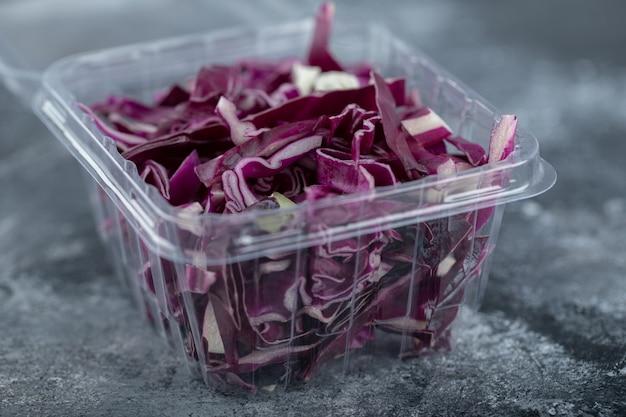 Zbliżenie na zdjęcie plastikowego pojemnika pełnego posiekanej fioletowej kapusty