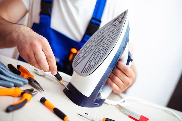 Zbliżenie na zdjęcie skoncentrowanego młodego mężczyzny, który naprawia uszkodzone żelazko w swoim miejscu pracy za pomocą narzędzi