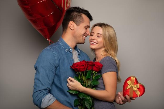Zbliżenie na zdjęcie słodkiej pary, która świętuje dzień świętego walentego, dając sobie prezenty i uśmiechając się ze szczęścia.