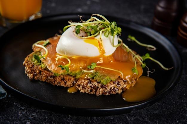 Zbliżenie na zdrowe tosty z łososiem i jajkiem w koszulce na czarnym tle