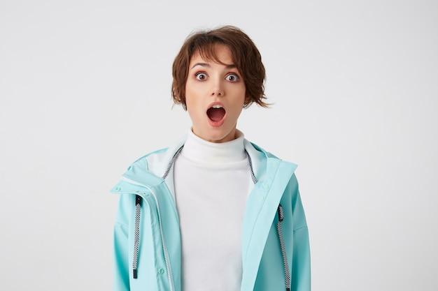 Zbliżenie na zdumioną krótkowłosą młodą kobietę w białym golfie i niebieskim płaszczu przeciwdeszczowym, stoi na białym tle z szeroko otwartymi ustami i zaskoczonym wyrazem twarzy, patrzy w kamerę z szeroko otwartymi oczami.