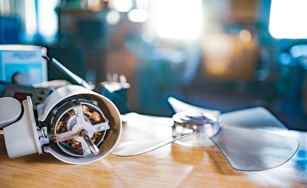 Zbliżenie na żelazny silnik z domowego wentylatora chłodzącego leży na stole podczas prewencyjnego czyszczenia, smarowania i naprawy w specjalistycznym warsztacie. koncepcja naprawy i odtworzenia uszkodzonego sprzętu