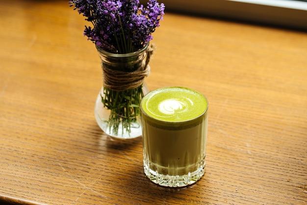 Zbliżenie na zielony napój matcha w szklance na drewnianym stole