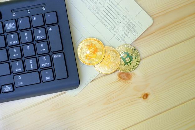 Zbliżenie na złote monety bitcoin na książeczce bankowej z klawiaturą laptopa na drewnianym stole