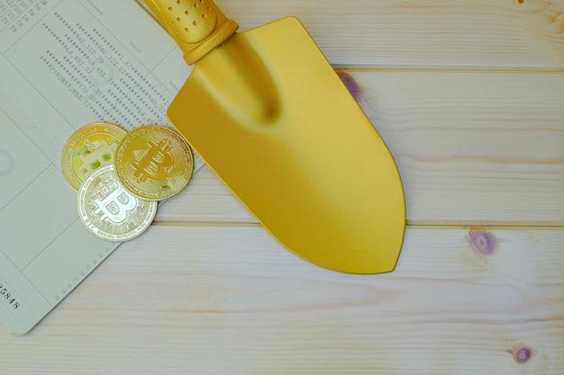 Zbliżenie na złote monety bitcoin w książeczce bankowej ze złotą łopatą na drewnianym stole
