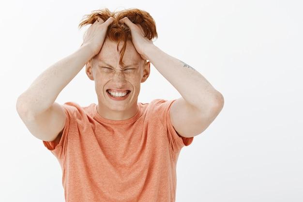 Zbliżenie na zmartwionego rudowłosego mężczyznę, który rzuca włosy i wygląda na skomplikowanego, ma problem