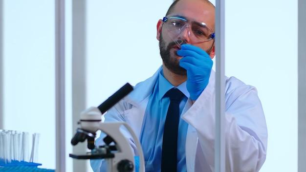 Zbliżenie na zmęczonego chemika mężczyzna lekarz pracujący w nowocześnie wyposażonym laboratorium naukowym. naukowiec pracujący z różnymi bakteriami, próbkami tkanek i krwi, badania farmaceutyczne nad antybiotykami