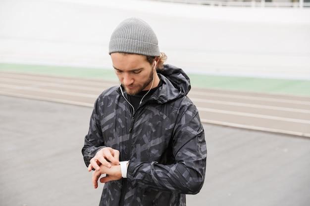 Zbliżenie na zmotywowanego młodego sportowca, który słucha muzyki przez słuchawki, stojąc na stadionie