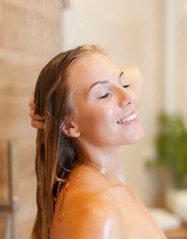Zbliżenie na zrelaksowaną kobietę pod prysznicem